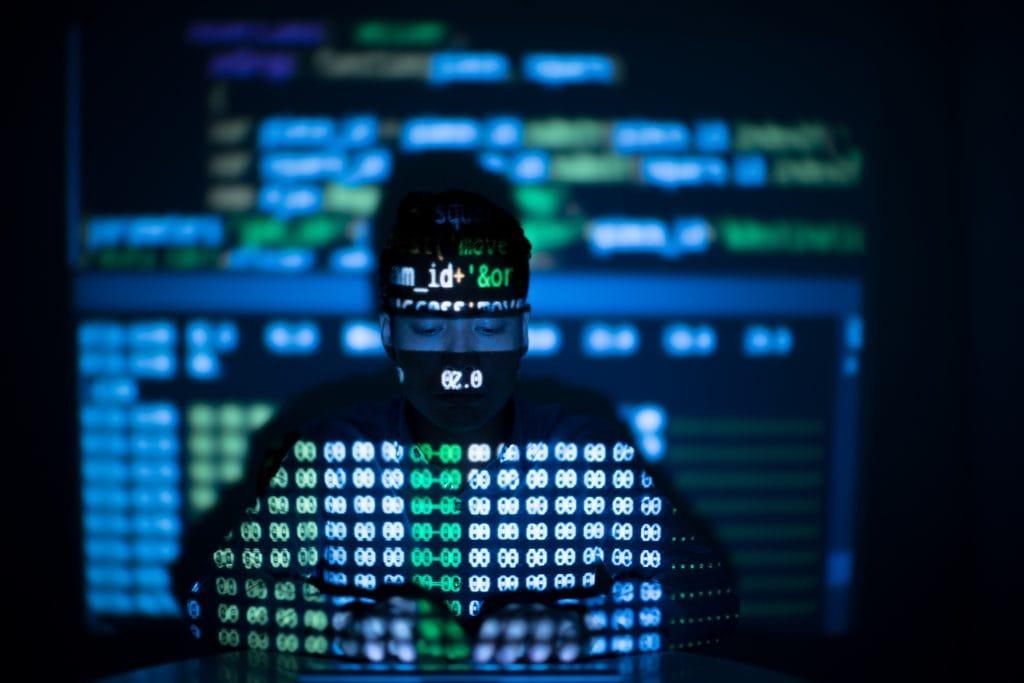 Dieses Bild zeigt einen Mann vor einem Computer, Code ist an die Wand projiziert.