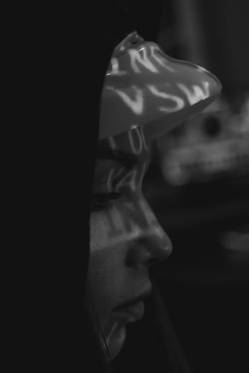 Das Bild zeigt einen Programmierer vor seinem Computer. Dieser tippt gerade etwas ein, die Atmosphäre ist dunkel.