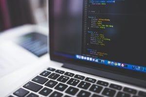 Das Bild zeigt einen Laptop, auf dem ein Computer-Programm geöffnet ist. Dort ist Computer-Code zu sehen.