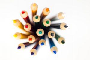 Das Bild zeigt Buntstifte von oben. Diese haben alle erdenklichen Farben.