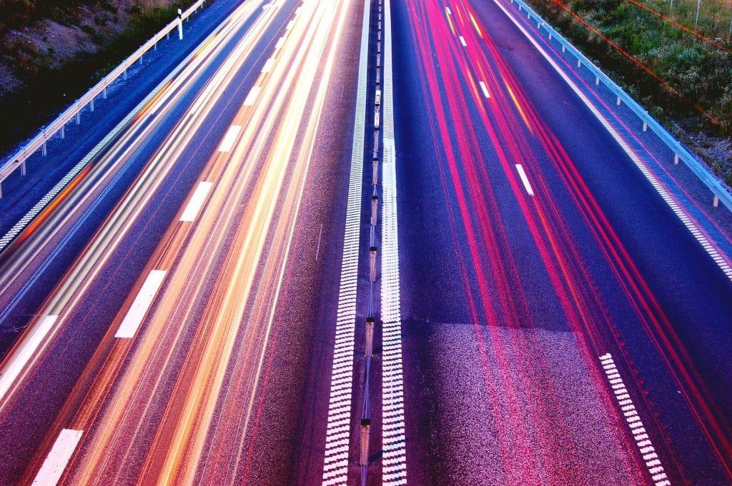 Das Bild zeigt eine Autobahn, die Lichter sind verschwommen. Keine Autos sind zu sehen, Schnelligkeit soll dargestellt werden.