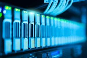 Es ist ein Server zu sehen, bei dem die Festplatten genauer belichtet werden. Es blinkt und Kabel sind zu sehen.