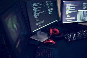 Dieses Bild zeigt einen Schreibtisch mit vielen Bildschirmen in kühler Athmosphäre.