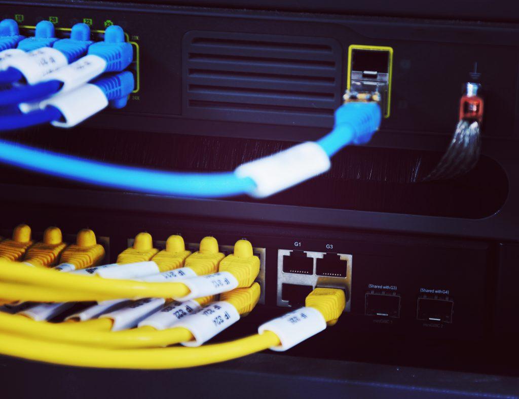 Zu sehen ist ein Server. Hier werden verschiedene Kabel in die dafür vorgesehenen Stecker gesteckt.